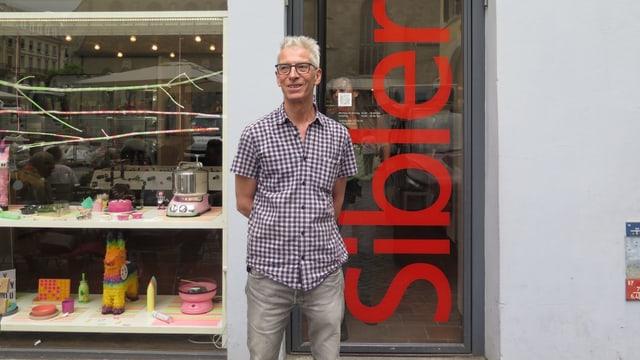 Ein Mann steht vor dem Eingang seines Geschäfts