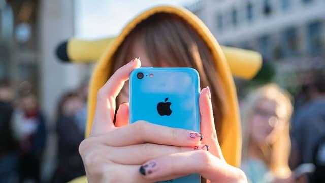 Eine Person in einem flauschigen Pikachu-Einteiler hält sich ein blaues iPhone vor's Gesicht.