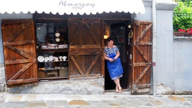Eine Frau mit blauer Schürze steht vor ihrem Souvenirladen.