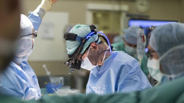 Szene in einem Operationssaal. Man sieht einen Arzt und Personal in grünen Kutten.