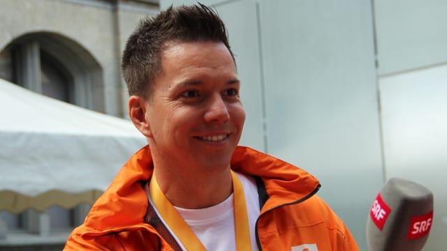 Ein lachender Sven Epiney mit Mikrofon.