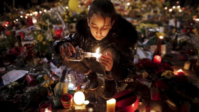 Trauernde zündet Kerze an.