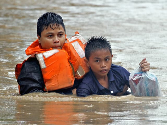 Mutter und Kind mitten im Wasser mit ihren Habseligkeiten.