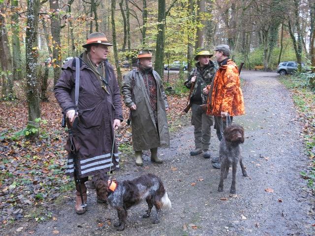 Männer mit Hunden im Wald.