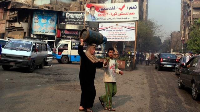 Eine Frau und ein Junge überqueren eine Strasse in Kairo.