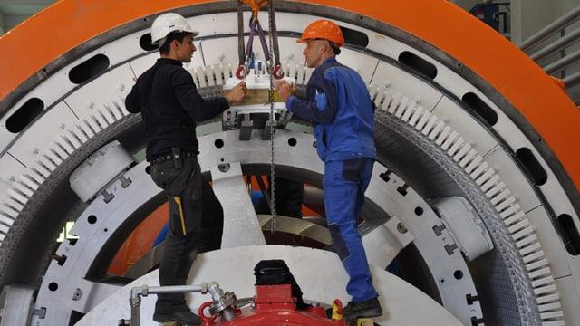 Dus lavurants en l'ovra electrica a Tinizong vi d'ina turbina.