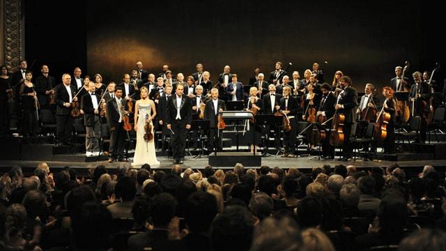 Ein Orchester im Konzertsaal, davor sitzt das Publikum.