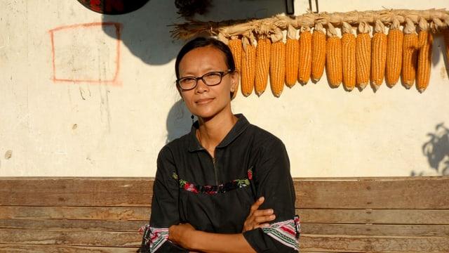 Eine Frua vor einer Mauer mit Maiskolben.