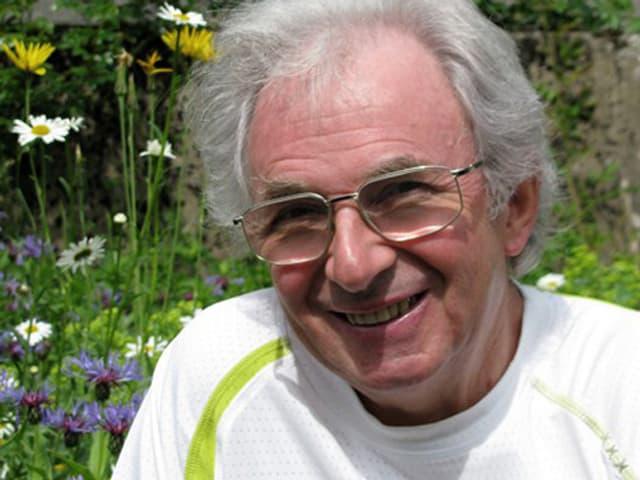 Lächelnder Mann mit Brille und grauen Haaren vor einer blühenden Wiese.