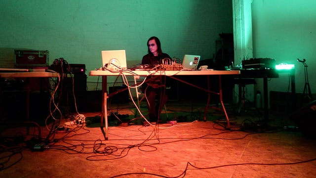 Ein Noise-Musiker vor zwei Laptopss und einem Synthesizer.