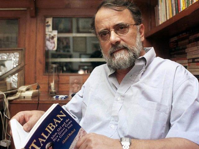 """Ahmed Rashid in seinem Arbeitszimmer, das Buch """"Taliban - Militant Islam, Oil and Fundamentalism in Central Asia"""" in den Händen haltend."""