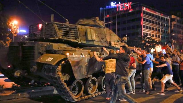 Anhänger von Präsident Erdogan versuchen, einen Panzer zu stoppen.