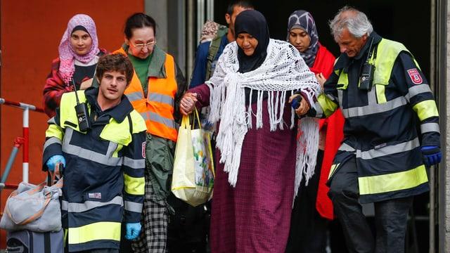 Am Bahnhof München helfen Helfer Flüchtlingen aus dem Zug zu steigen