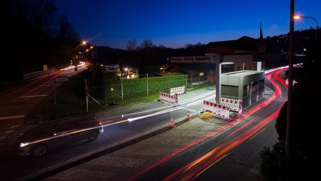 Ein Grenzübergangsposten bei Nacht, Licht von Scheinwerfern.
