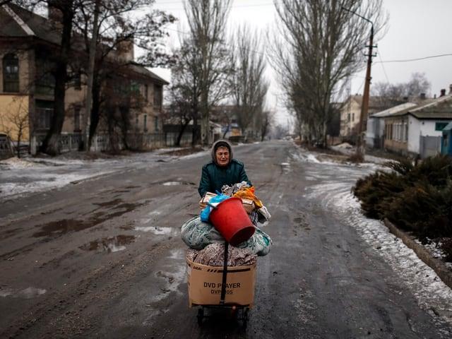 Eine Frau schiebt in einer leeren Strasse auf einem Karren ihre Habseligkeiten vor sich her.