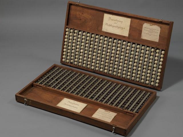 Ein Holzkasten mit den weissen und schwarzen Kugeln, eingeklebt Zettel mit der Anweisung zur Handhabung.