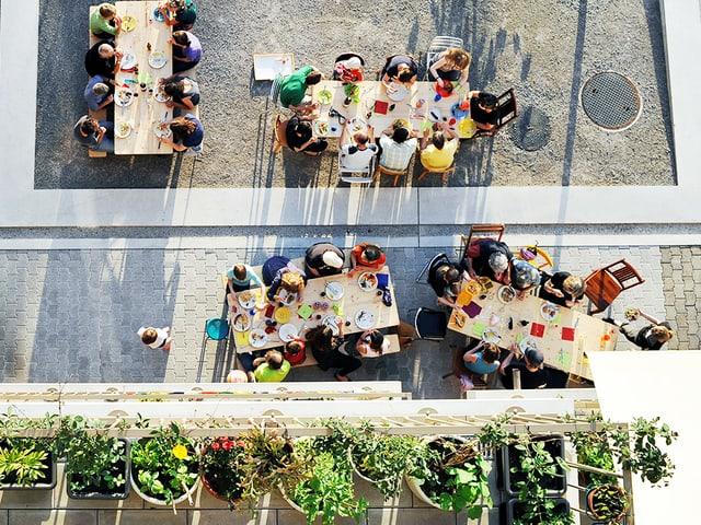 Blick von oben auf Pflanzen und Menschen, die an bunt bedeckten Tischen sitzen.