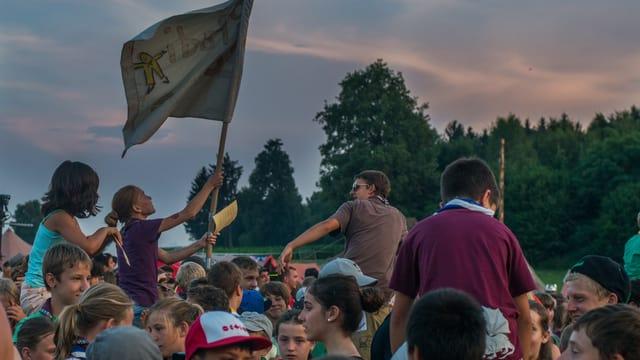 Kinder als Pfadfinder draussen mit einer Fahne bei der Eröffnungszeremonie des Lagers vor einem Wald.