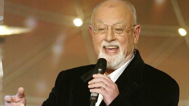 Ein Sänger mit grauen Haaren und Brille mit Mikrofon bei einem Auftritt.