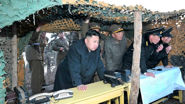 Kim Jong Un mit Militärs in einem Unterstand unter einem Tarnnetz.