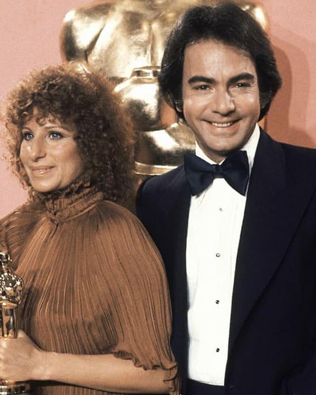 Barbra Streisand und Neil Diamonds posieren als Erwachsene lächelnd für die Kameras. Streisand hält ein goldenes Oscar-Männchen in der Hand.