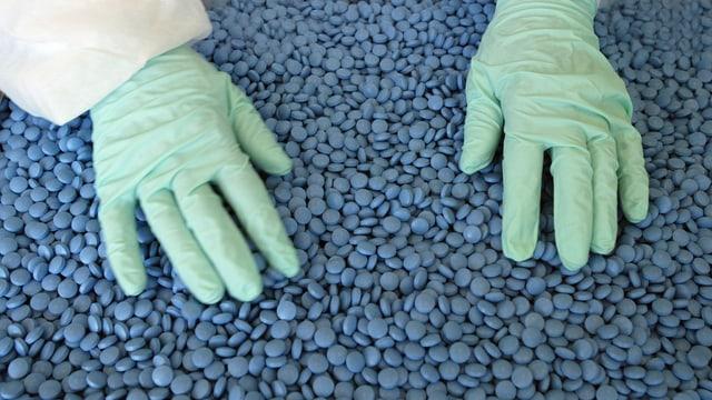 Hände in Handschuhen durchmischen einen Berg von blauen Tabletten.