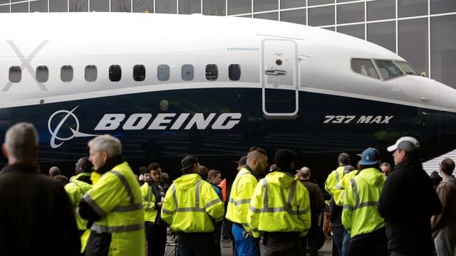 Leute in gelben Westen stehen auf einem Flugfeld vor einer Boeing 737 Max 8.