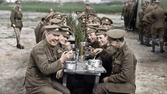 Lachende Soldaten am Mittagstisch während des Ersten Weltkriegs.
