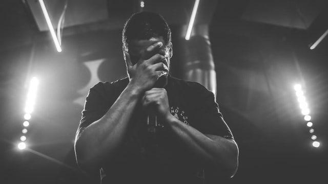 schwarzweissbild eines rappers auf der bühne, der sein gesicht mit einer hand verbirgt