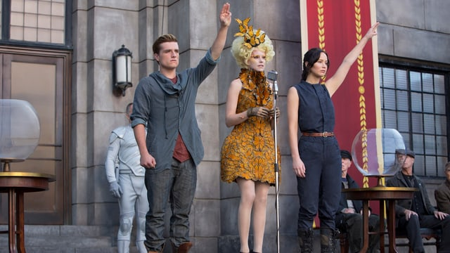 Szene aus Hunger Games, die beiden Hauptfiguren mit erhobenem linken Arm.