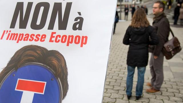 Ein Mann und eine Frau stehen neben einem Antio-Ecopop-Plakat auf Französisch.