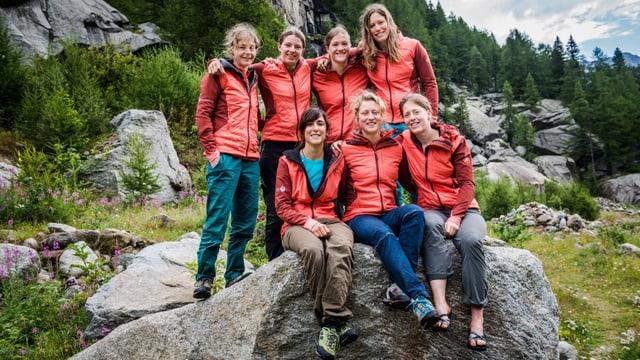 Frauen sitzen auf Stein in den Bergen.