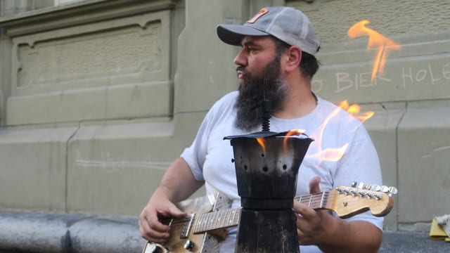 Ein Mann mit Käppi spielt Gitarre.