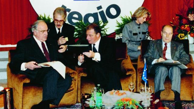 Bundeskanzler Helmut Kohl, Bundespräsident Jean-Pascal Delamuraz und Staatspräsident François Mitterand sitzen auf einer Polstergruppe.