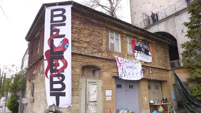 Ein älteres Haus mit Spalier, daran hängen Transparente.