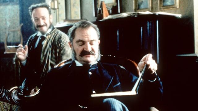 Ein Mann auf einer Couch schaut in ein Buch, ein zweiter neben ihm raucht und lacht.
