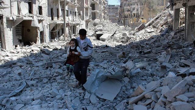 Kein Stein mehr auf dem anderen in Aleppo. Ein Mann trägt ein Mädchen über Trümmer.
