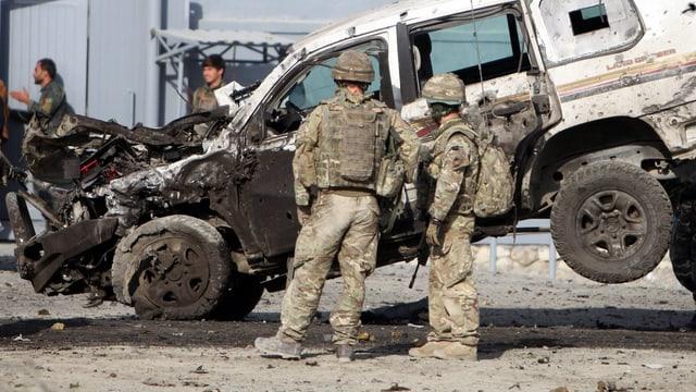 Sicherheitskräfte stehen vor einem demolierten Auto