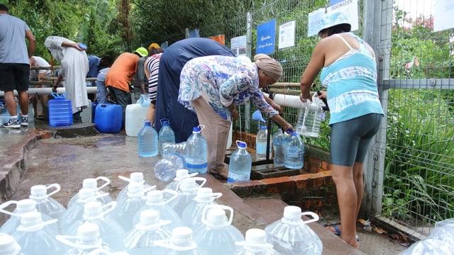 Personen füllen Wasserflaschen und -kanister mit Wasser.