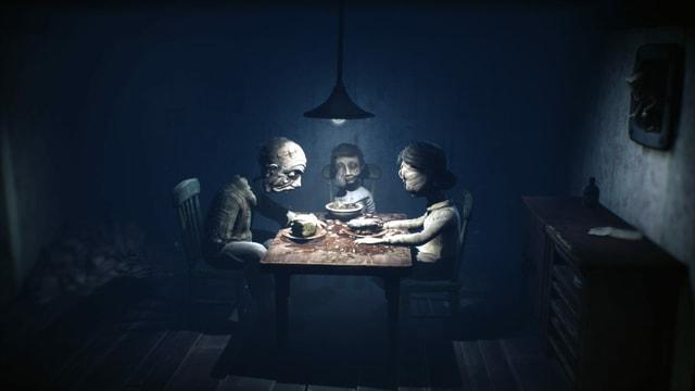 Eine gruselige Horror-Puppen-Familie sitzt bei einem düsteren Abendmahl zusammen.