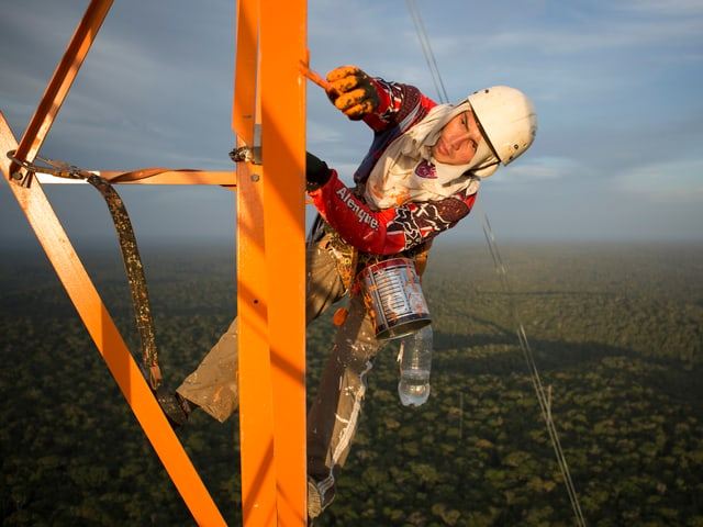 Ein Mann bemalt den Stahlurm in schwindelerregender Höhe.
