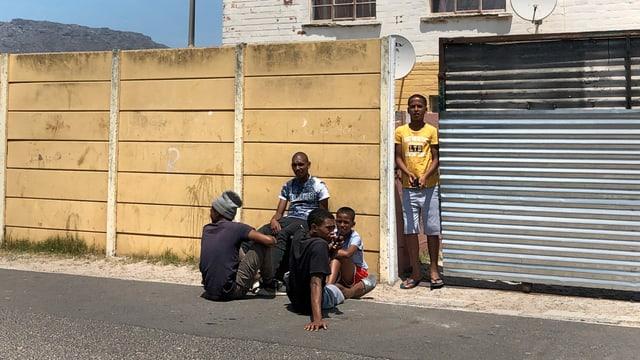 Eine Gruppe Männer sitzt vor Wand