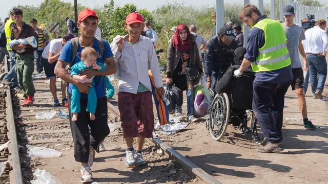 Zwei Männer überqueren mit einem Baby die Grenze nach Ungarn.