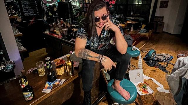 ein junger Mann mit langen Haaren sitzt in einem chaotischen Zimmer