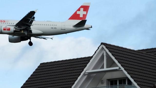 Ein Flugzeug fliegt knapp über das Dach eines Einfamilienhaus.