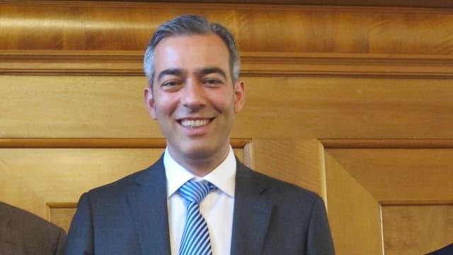 Mann mit blauer Krawatte und Anzug und grauen Haaren lächelt