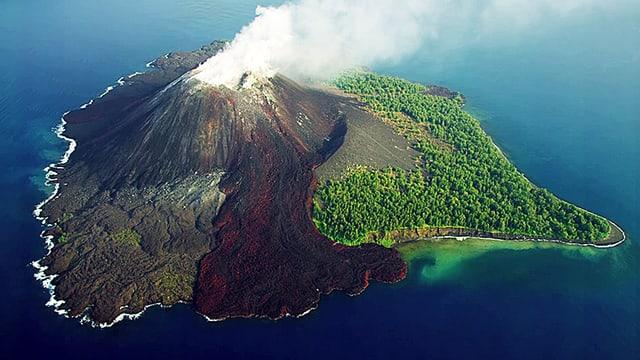 Auf einer Vulkaninsel sind unberührte Wälder, ein heisser Lavastrom und abgekühltes Lava gleichzeitig zu sehen.
