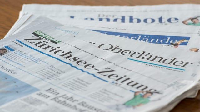 Titelseiten der drei Regionalzeitungen Zürichsee-Zeitung, Zürcher Oberländer und Landbote auf einem Tisch fotografiert