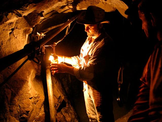 Minenarbeiter schaltet im Stollen Licht an.