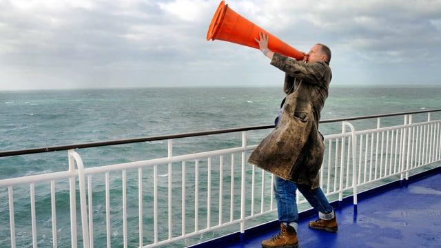 Ein Mann steht an der Reling, hält einen Leitkegel an den Mund und ruft auf das Meer hinaus.